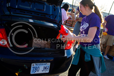 Madison Williams, junior in Finance, places a few bags of chips in the trunk of the car at the Mobile Food Pantry sponsored by HandsOn K-State on Feb. 10. The Mobile Food Pantry is aimed at providing food securtiy for Riley County and K-State affliated residents, where residents can drive up to an open line of foods. (Alanud Alanazi | The Collegian)