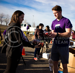 Cody Holthoas, junior in Business Management and Human Resources, hands a box of strawberries to a resident at the Mobile Food Pantry sponsored by HandsOn K-State on Feb. 10. The Mobile Food Pantry is aimed at providing food securtiy for Riley County and K-State affliated residents. (Alanud Alanazi | The Collegian)