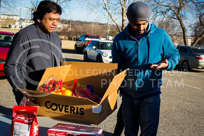 Two manhattan residents prepare load thier box eith food they've gathered from the Mobile Food Pantry sponsored by HandsOn K-State on Feb. 10. The Mobile Food Pantry is aimed at providing food securtiy for Riley County and K-State affliated residents. (Alanud Alanazi | The Collegian)