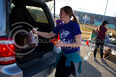 Madison Williams, junior in Finance, places a few bags of chips and bread in the trunk of the car at the Mobile Food Pantry sponsored by HandsOn K-State on Feb. 10. The Mobile Food Pantry is aimed at providing food securtiy for Riley County and K-State affliated residents, where residents can drive up to an open line of foods. (Alanud Alanazi | The Collegian)
