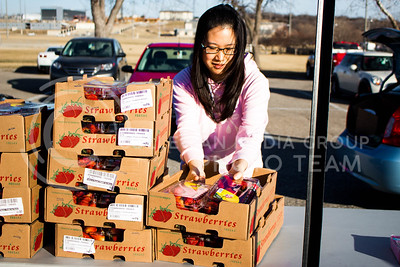 Sarocha Pradyawong, PhD Graduate in Biological and Agriculture Engineering, picks up two boxes of strawberries to distribute at the Mobile Food Pantry sponsored by HandsOn K-State on Feb. 10. The Mobile Food Pantry is aimed at providing food securtiy for Riley County and K-State affliated residents. (Alanud Alanazi | The Collegian)