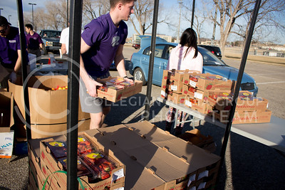 Cody Holthoas, junior in Business Management and Human Resources, carries a box of strawberries to distribute at the Mobile Food Pantry sponsored by HandsOn K-State on Feb. 10. The Mobile Food Pantry is aimed at providing food securtiy for Riley County and K-State affliated residents. (Alanud Alanazi | The Collegian)