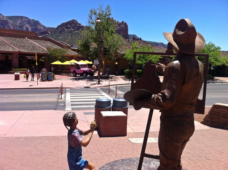 A photo of a statue of a kid taking a photo of a statue of a man painting a picture of a mountain.