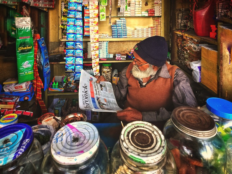 Shop vendor's portrait while he is reading the news