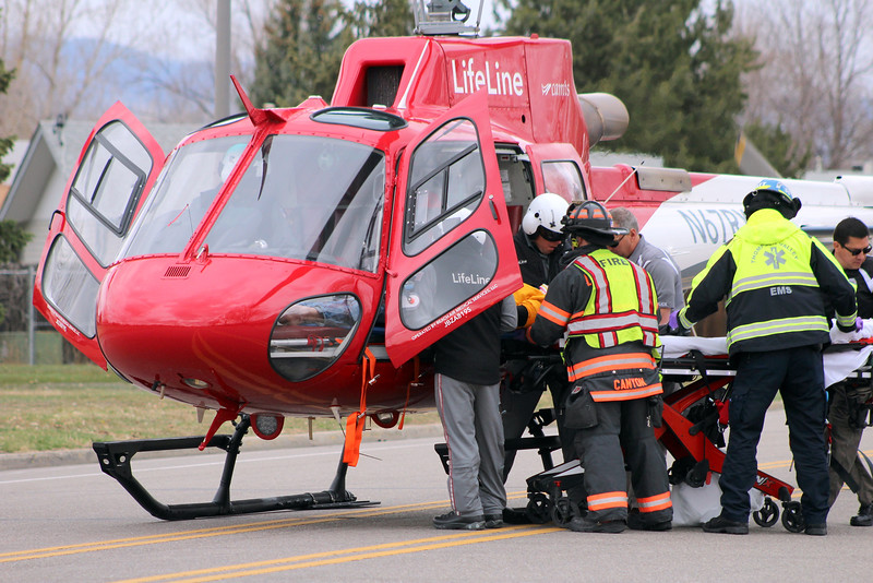 Emergency personnel load a mock crash victim, played by Thompson Valley student Jay Denning, into a Life Line helicopter as students watch Wednesday, March 28, 2018, outside the school in Loveland. (Photo by Hans Peter/Loveland Reporter-Herald)