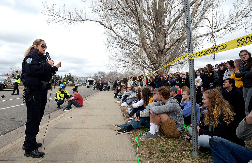 . Loveland Police Officer Antolina Gonzales, left, talks to Thompson Valley students about drunk driving as they watch emergeny personnel help mock crash victims Wednesday, March 28, 2018, outside the school in Loveland. (Photo by Jenny Sparks/Loveland Reporter-Herald)