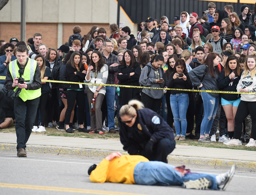 . Thompson Valley High School students watch as Loveland Police Officer Antolina Gonzales checks on a mock crash victim laying in the street Wednesday, March 28, 2018, outside the school in Loveland. (Photo by Jenny Sparks/Loveland Reporter-Herald)