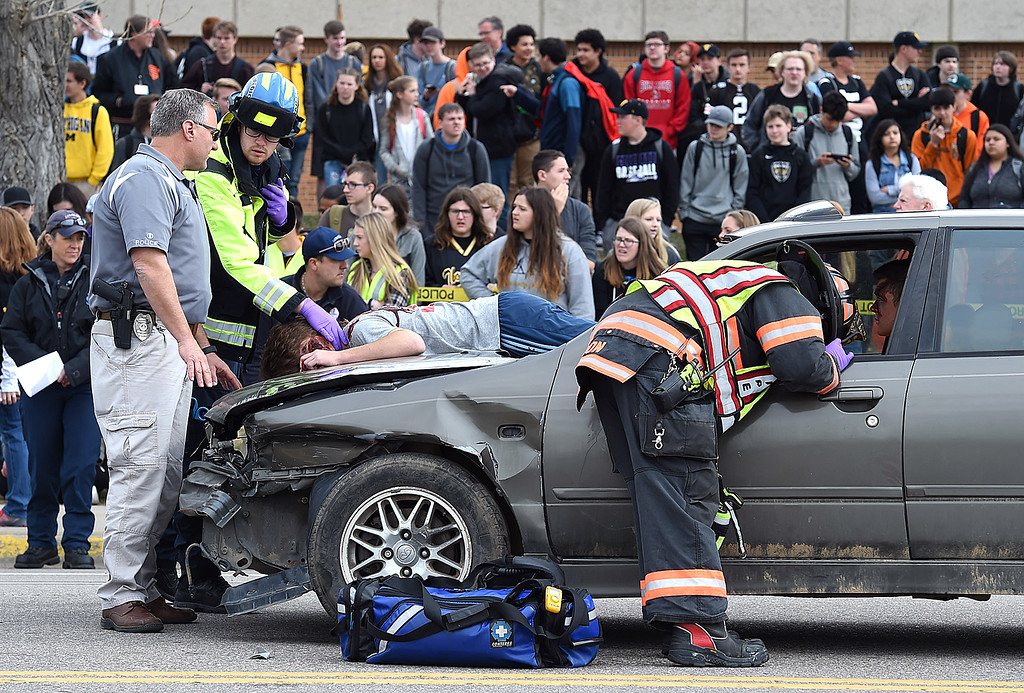 . Emergency personnel including Loveland Police, Thompson Valley Emergency Services paramedics and Loveland Fire Rescue Authority firefighters check on mock crash victims Wednesday, March 28, 2018, as students watch outside the school in Loveland. (Photo by Jenny Sparks/Loveland Reporter-Herald)