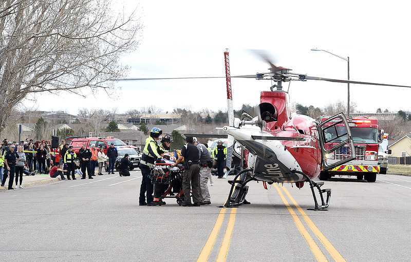 Emergency personnel load a mock crash victim, played by Thompson Valley student Jay Denning, into a Flight for Life helicopter as students watch Wednesday, March 28, 2018, outside the school in Loveland. (Photo by Jenny Sparks/Loveland Reporter-Herald)