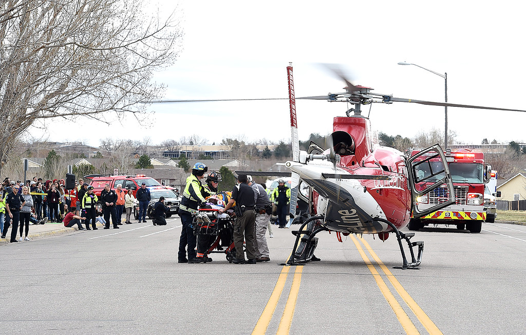 . Emergency personnel load a mock crash victim, played by Thompson Valley student Jay Denning, into a Flight for Life helicopter as students watch Wednesday, March 28, 2018, outside the school in Loveland. (Photo by Jenny Sparks/Loveland Reporter-Herald)