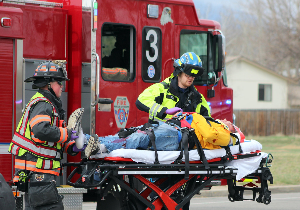 . Emergency personnel secure a mock crash victim, played by Thompson Valley student Jay Denning, to a gurney students watch Wednesday, March 28, 2018, outside the school in Loveland. (Photo by Hans Peter/Loveland Reporter-Herald)