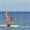 Woman practices yoga as she balances on her hands with one leg up on a paddle board in the Gulf of Mexico.