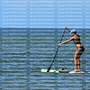 Beautiful woman paddleboards on the Gulf of Mexico on Fort Myers Beach, Florida, USA.
