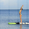 Woman practices yoga on a stand up paddleboard in the Gulf of Mexico.