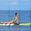 Beautiful woman arches her back as she practices yoga on a paddle board also called a sup.