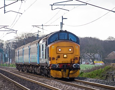 The 10.04 Preston to Barrow hurries north along the WCML at Woodacre (Garstang) behind DRS Class 37, 37409 on 24th February 2017.