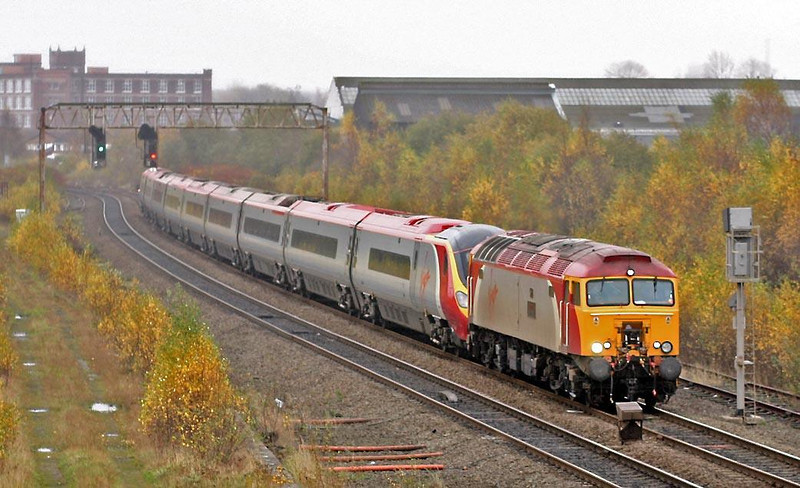 In the gloom of an early November Sunday afternoon 57306 drags 390036 through Bolton with a late running WCML express, 7th November 2004.  Image supplied by Peter Kellett.