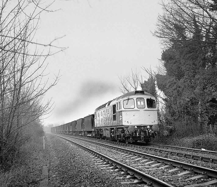 33x (33004?) drags a rake of bogie ballast hoppers away from Milford (Salisbury) on the Romsey line.  January 1985.  Rolleicord Va Tri-X.  Image supplied by Chris Nevard.