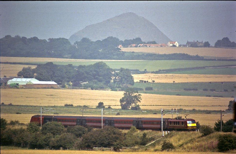 Berwick Law stands prominent on the horizon as a North Berwick service returns to the mainline ar Drem on 2nd August 2004.  Image supplied by Peter Kellett.