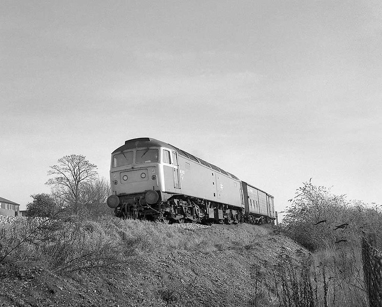 47147 on a rather light freight working passing the site of salisbury MPD.  Late Autumn 1983.  Rolleicord HP5.  Image supplied by Chris Nevard.