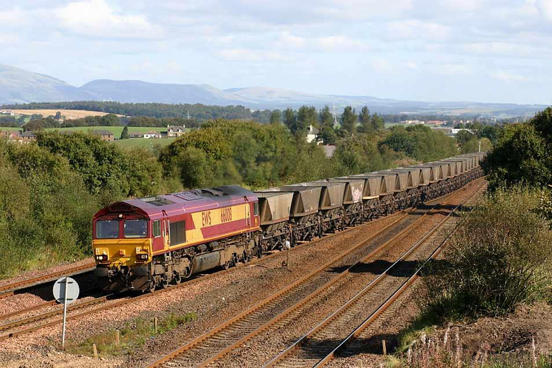 A Class 66 crossing over onto the Cumbernauld line at Greenhill Lower with an empty HAA rake. 66008 15th September 2004. Image supplied by Peter Kellett