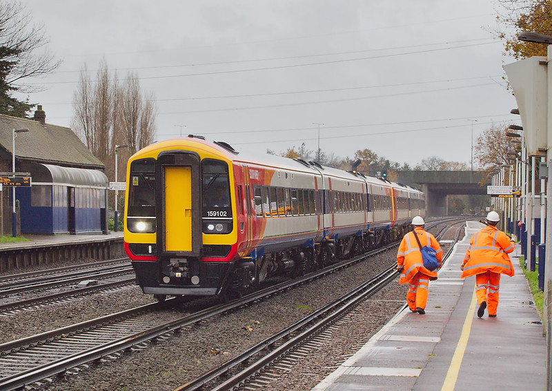 5th Dec 06: 159102 and 159017 race to Waterloo with the 08.20  service from Yeovil .   Byfleet & New Haw
