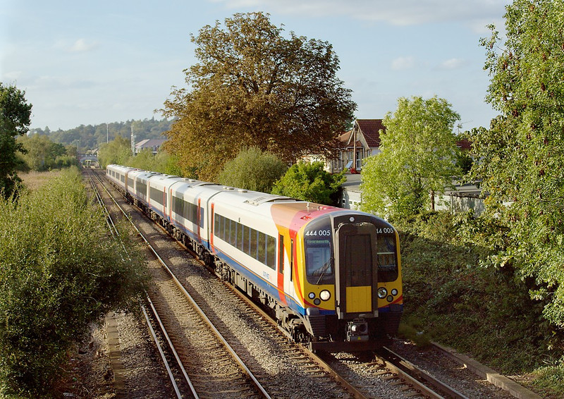 7th Oct 06:  With the shaddows lenthening diverted  444005 for Bournmouth leads 444011 for Portsmouth Harbour across Addlestone Moor.  8th
