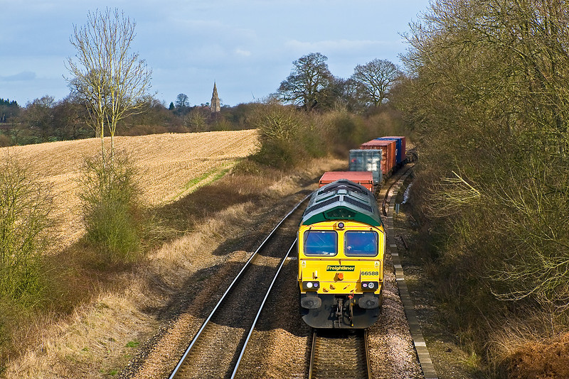 2ndnd Feb 08:  With Mortimer church and the Reading Wind Turbine in the background 66588 rounds the curve through Silchester. 05.29 from Garston.