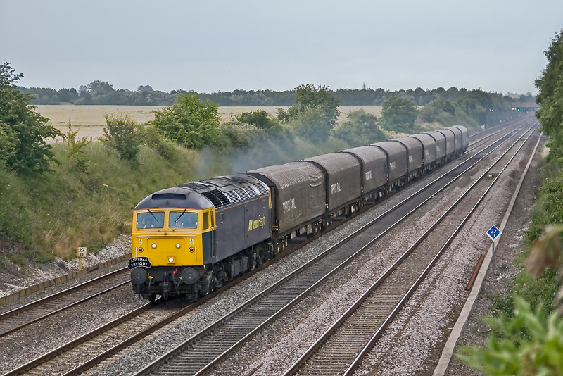 17th Jul 08:  In very poor light 57006 heads west to Gloucester with the returning empties of the trial service of coiled wire from Cardiff to Ripple Lane. Captured here at Shottsbrooke