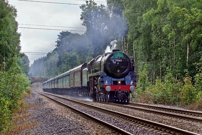 13th Aug 09:   The Cathedrals Express from Victoria to Oxford via Redhill (1Z88) powered by 70013 'Oliver Cromwell' climbs away from Sandhurst towards Crowthorne.