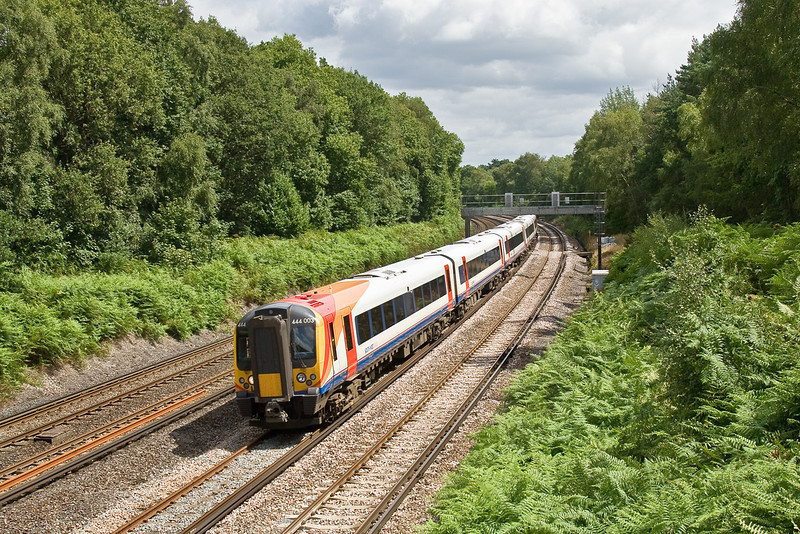 3rd Aug 09:  444003 forms the 12.35 From Waterloo to Weymouth (1W25). Captured here rounding the curve through Pirbright
