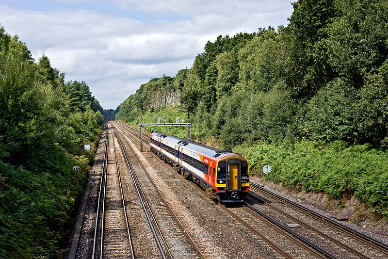 18th Aug 09:   159011 cruises through Pirbright with a service to Waterloo from Yeovil Junction