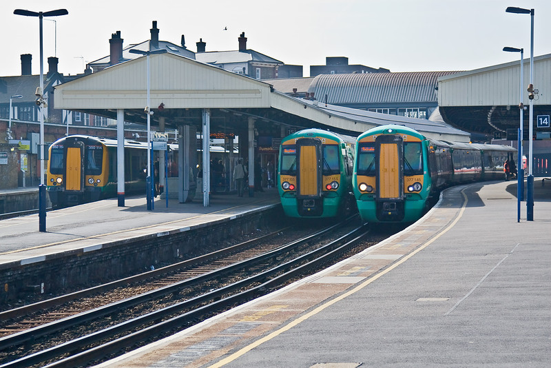 18th Mar 09:  London Midland Desiro 350114 waits to depart as Southrn's 377155 and 377145 cross at Clapham Junction