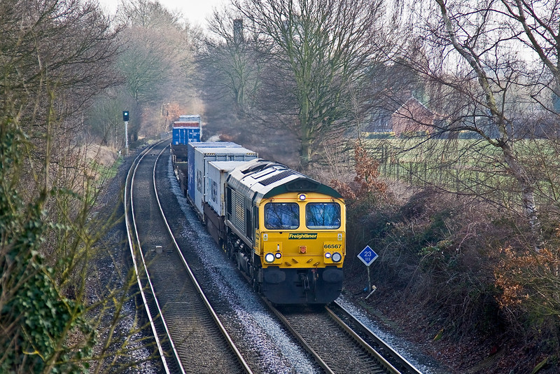29th Jan 09:  The 4M58, 12.28 from Southampton to Ditton now runs via the SWML and the WCML. Today powered by 66567 it is captured here at Lyne.  The pillars of the M25 bridge can be seen in the backgound.