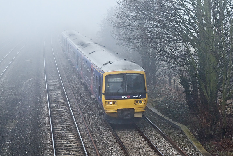 14th Jan 09:  166217 forming  the 11.37 from Oxford looms out of the fog as it runs through Lower Basildonb
