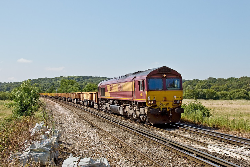 24th Jun 09:  66103 is tasked with the Eastleigh to Hoo Junction Departmental consisting of a long rake of JNA, MLA & MTA ballast wagons. Captured here nearing Prune Hill Crossing in Egham.