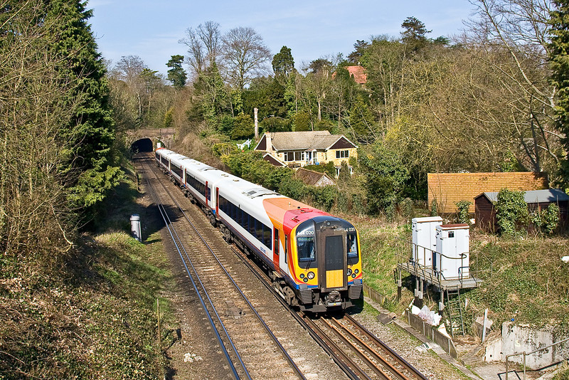 20th Mar 09:  The 12.15 from Waterloo to Haselmere leaves the 1st of the two tunnels at Guildford,  Network Rail boxes have not improved this shot.