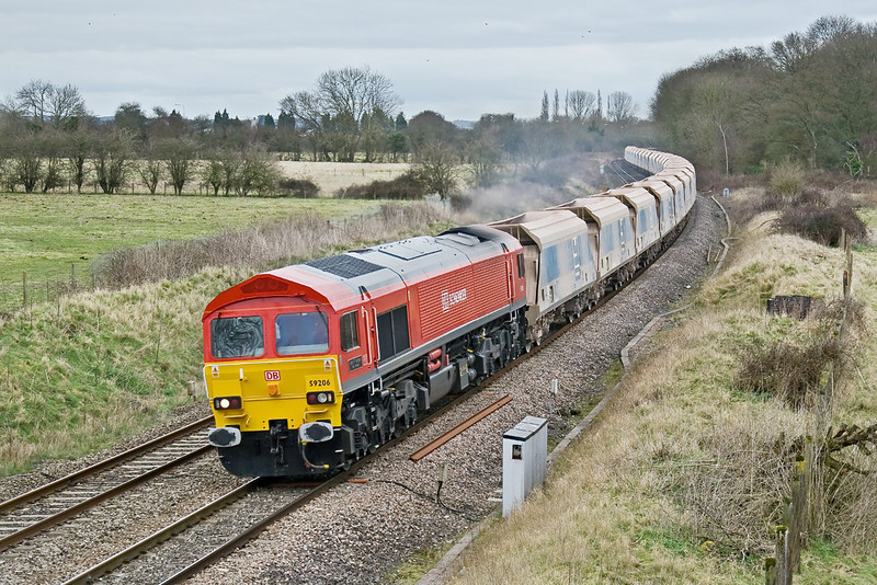 13th Mar 09:  Providing a splash of colour on a dull day is 59206 heading west with a monster load of empties, working 7C77 from Acton to Merehead. There are 16 boxes after the visible 27 hoppers !  Frouds Lane