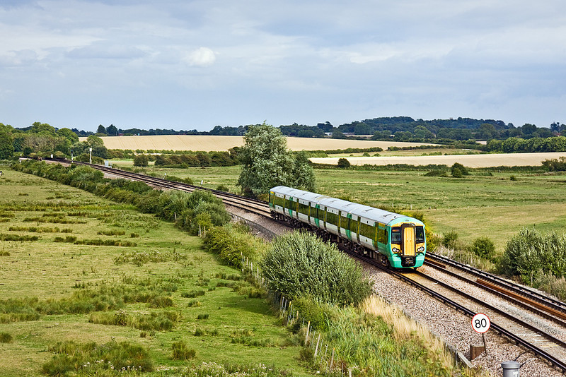 12th Aug 10:  Having started from Victoria as 1H30 to Littlehampton the rear set is continuing to Eastbourne as 1F34 the 16.07 from Haywards Heath.  Seen here having just crossed the site of Beddingham level crossing