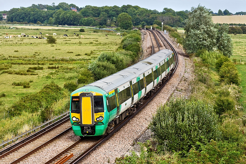 12th Aug 10:  The 16.22 from Ore to Brighton is nearing Lewes as it runs through Beddingham formed of 377459
