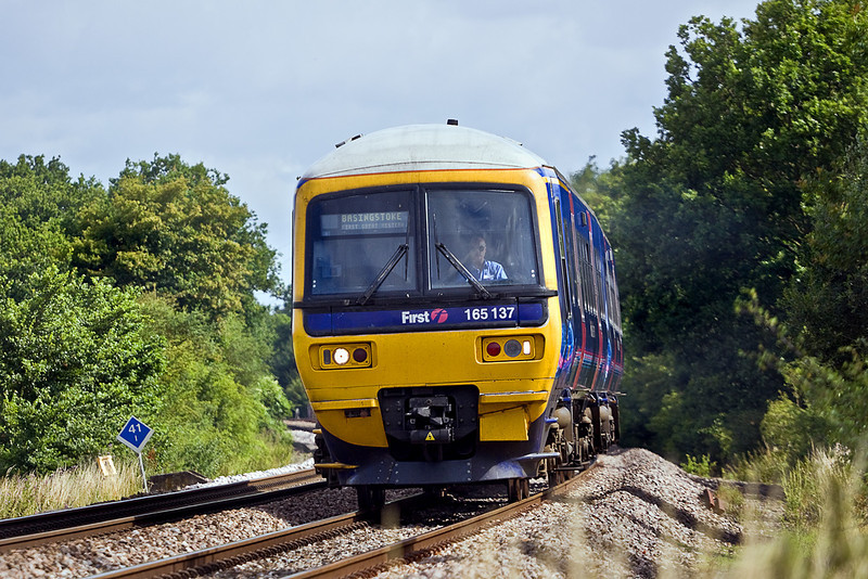 17th Jul 10:  The 09.39 shuttle service from Reading to Basingstoke provided by 165137 is seen here  passing through Grazeley