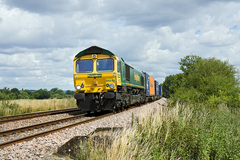 "17th Jul 10:  66570 rushes south over ""Danes"" foot crossing in Grazeley on 4O27 from Garston"