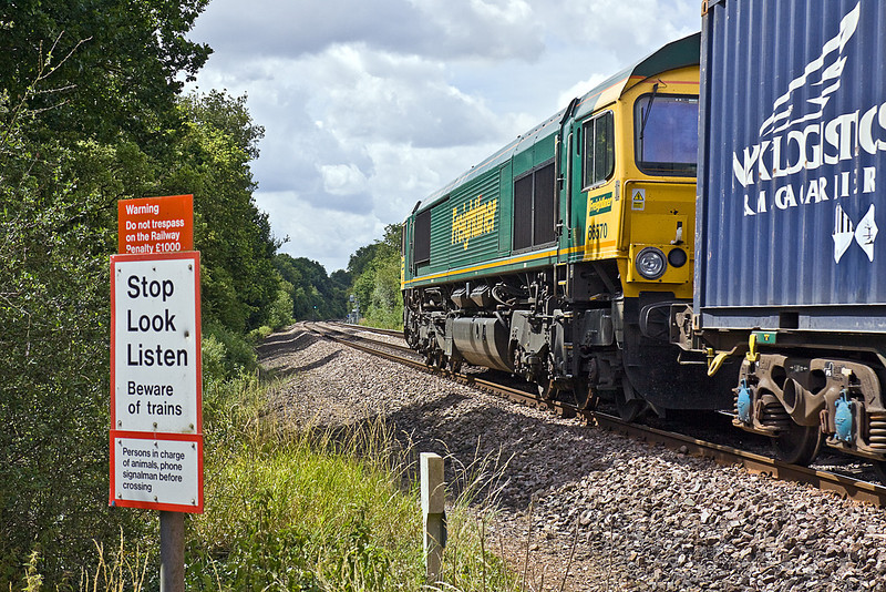 17th Jul 10:  66570 rushes south over 'Danes Crossing' near Grazeley with 4O27 from Garston to Southampton