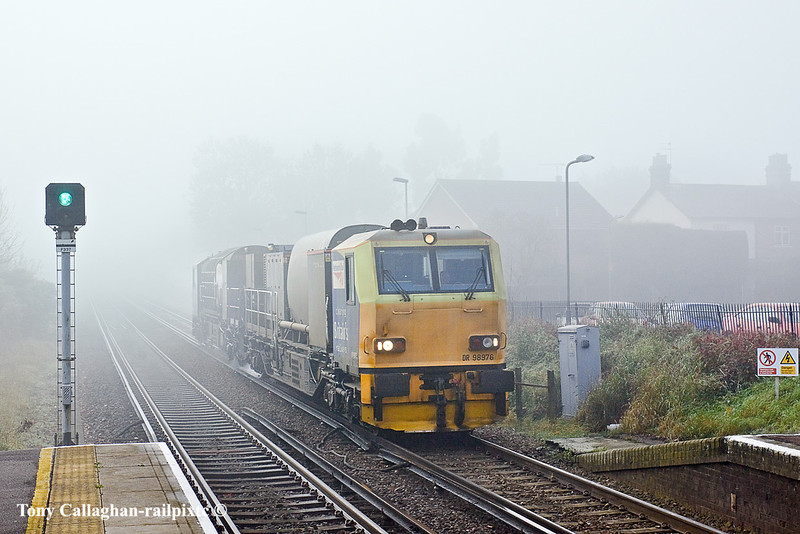 16th Nov 10:  On a cold and foggy morning  Effingham Junction's RHTT MPV DR98976 & 926 are working 3S82.   Captured here as it runs through Bagshot towards Ascot