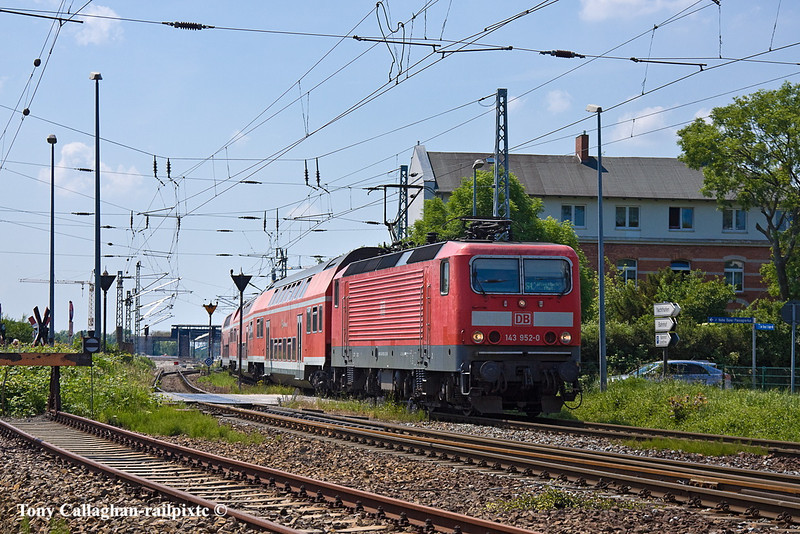 5th Jun 11:  143 952-0 crosses over the level crosing in Alt Bahnhofstrasse on the approach to the Station at Warnemunde.