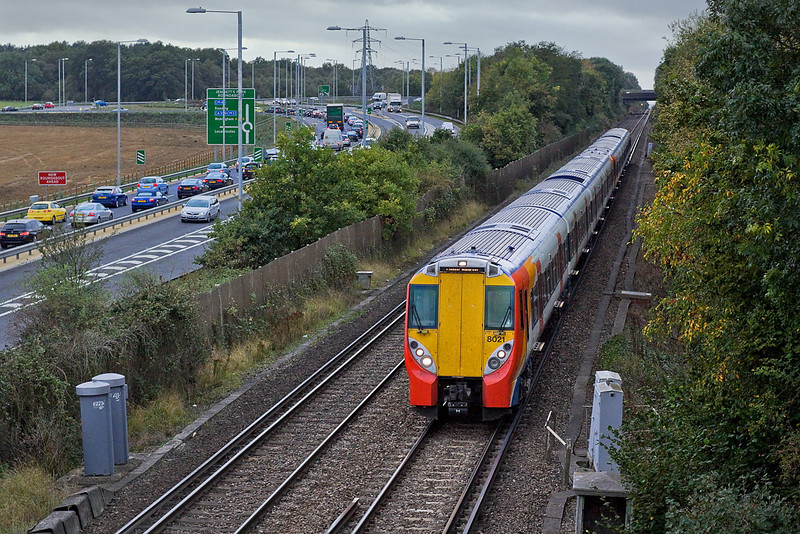 11th Oct 11:  458021 leads on 2C56 the 17.09 from Reading to Waterloo.  Traffic is building up on the southbound A329 at Bracknell's Amen Corner.  Shot settings  Manual Exp, 1/500 @ f4.  50mm f1.4 prime.  iso 800
