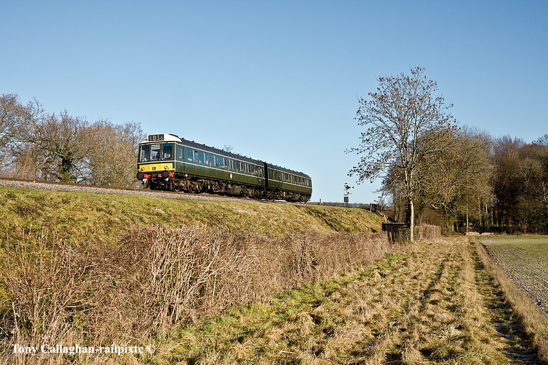 9th Jan 11:  The class 117 Pressed Steel DMU forming the 10.50 from Alton runs down hill and over Bowers Green Road in North Street near Ropley