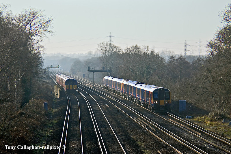 21st Jan 11:  In soft winter light 450030 working the 12.28 from farnham to Waterloo passes  a 455 on a Guildford stopper.  Pictured fron Locke King Road in Weybridge