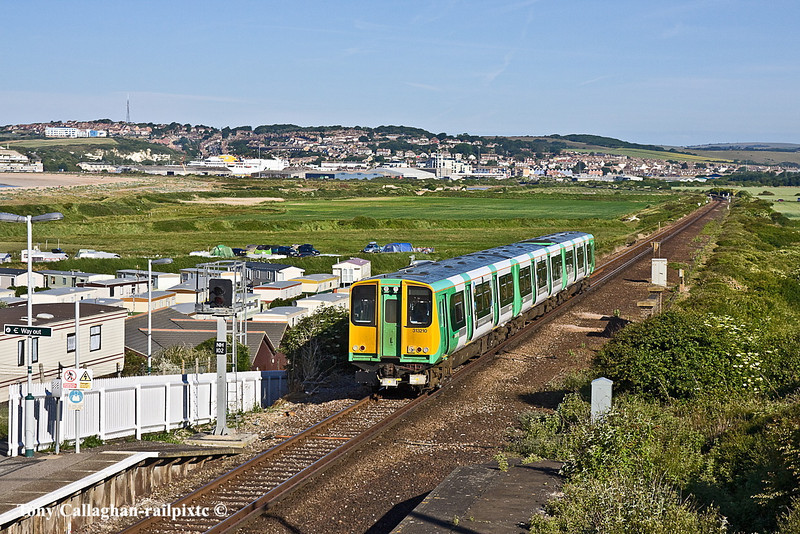 3rd Jun 11:  313120 is arriving at Bishopstone working 2F41 the 07.17 from Brighton to Seaford.  in the distance,  gleaming in the morning sunshine, can be seen the Newhaven to Dieppe ferry.