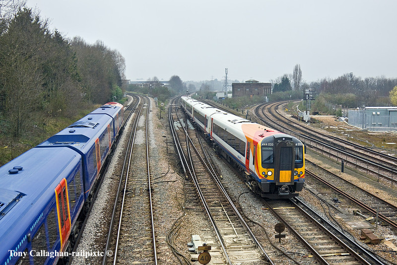 16th Mar 11:  As the 12.00 fto Ascot climbs away up the hill the 11.30 from Waterloo to Portsmouth Harbours formed of 444035 slows for the Guildford stop